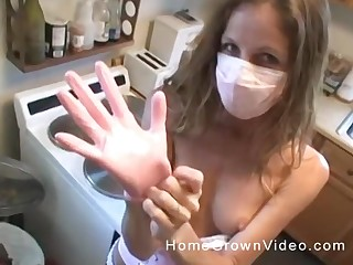 Kinky light-complexioned housewife puts on a mask and gloves and strokes a flannel